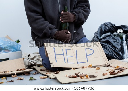 Homeless alcoholic sitting around the trash bags and holding an empty bottle - stock photo