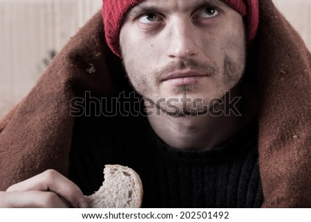 Homeless and hungry man eating a piece of bread - stock photo