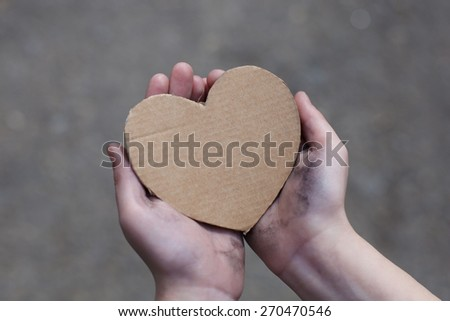 homeless boy holding a cardboard heart, dirty hand - stock photo