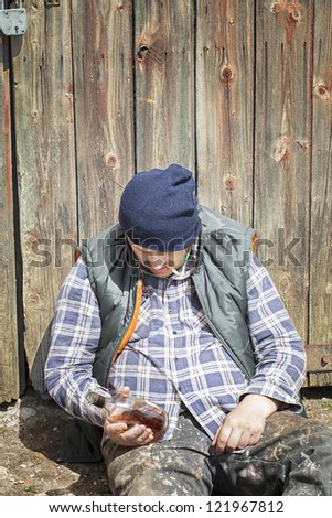 Homeless leaning against barn door - stock photo