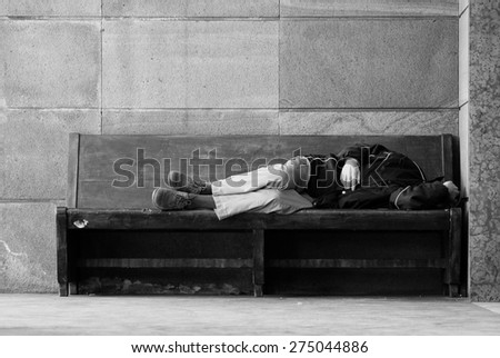 Homeless lying on a wooden bench - stock photo