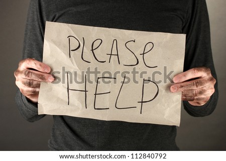 homeless man asks for help, on black background close-up - stock photo