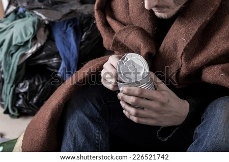 Homeless man covered with a blanket eat a meal - stock photo
