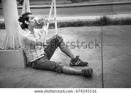 Homeless man drinking water on street,Unemployed