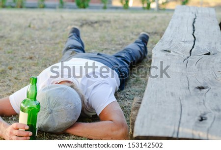 Homeless man fallen down on the ground next to a bench in the park, experiencing lethargy after excessive drinking - stock photo