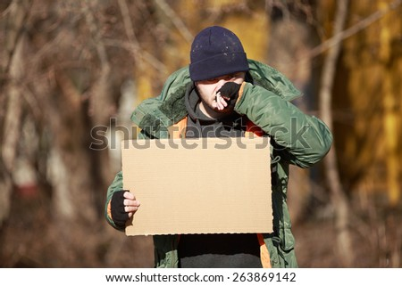 Homeless man holds blank cardboard for your text - stock photo