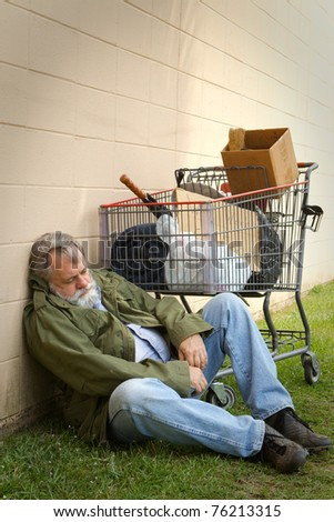 Homeless man leans against a wall sleeping with a grocery basket next to him containing his belongings. - stock photo
