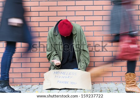 Homeless man sitting on a street passed by people - stock photo