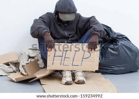 Homeless man sitting on a street with sign - stock photo