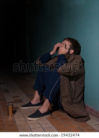 Homeless man sitting on floor - stock photo