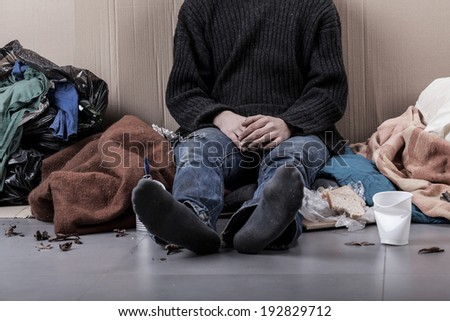 Homeless man sitting on the street, horizontal