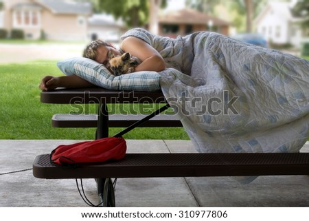 Homeless man sleeping on a picnic table in the city park holding his pet dog.