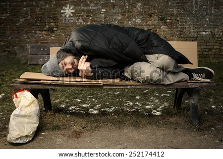 Homeless man sleeping on bench in winter park - stock photo