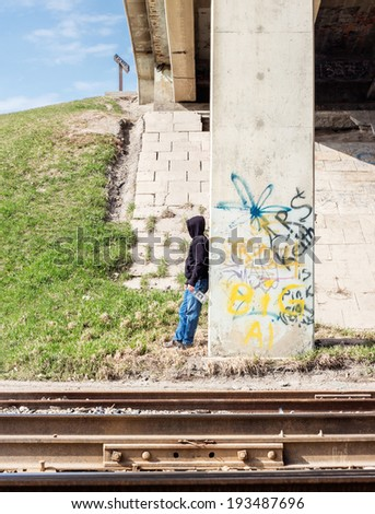 homeless man with a whiskey bottle standing against a stone wall with graffiti written on it wearing a black hoodie and jeans . - stock photo
