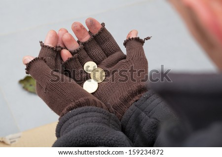 Homeless person holding a few cents in his hands - stock photo