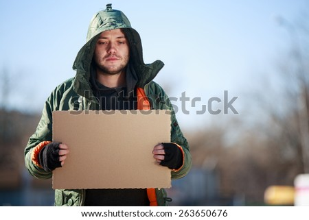 Homeless person with blanck cardboard. Focused on cardboard - stock photo