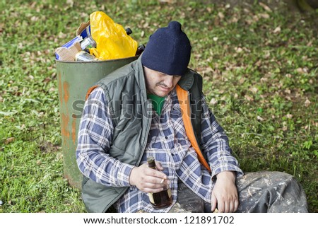 Homeless with botle of drink in hand leaning against garbage bin - stock photo