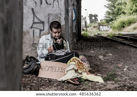 Homeless woman with sign sitting near the rail track and smoking