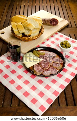 Homelike appetizer with salami, bread, olives, cheese, pickles and red wine - stock photo