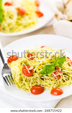 Homemade angel hair pasta with pesto sauce and roasted cherry tomatoes.