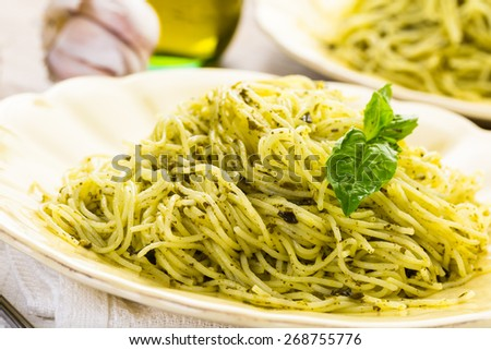 Homemade angel hair pasta with pesto sauce and roasted cherry tomatoes. - stock photo