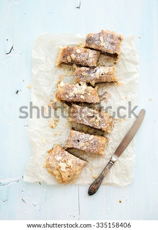 Homemade apple and almond strudel on baking paper over light blue wooden backdrop, top view - stock photo