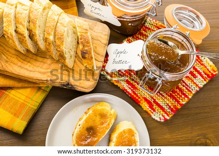 Homemade apple butter and freshly baked bread on the table. - stock photo