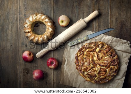 homemade apple pie on parchment paper with apples on old wooden dark table rustic style - stock photo