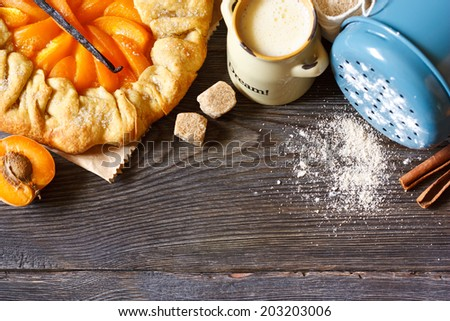 Homemade apricot pie with vanilla and brown sugar on a wooden background with food ingredients for baking. - stock photo