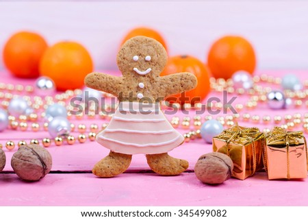 Homemade baked Christmas gingerbread man on vintage wooden background. Anise, cinnamon and decoration utensils. - stock photo