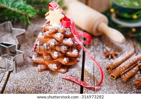 Homemade baked Christmas gingerbread tree on vintage wooden background. Anise, cinnamon, baking roll, star forms and decoration utensils. With icing sugar as snow. Selfmade gift for xmas. - stock photo