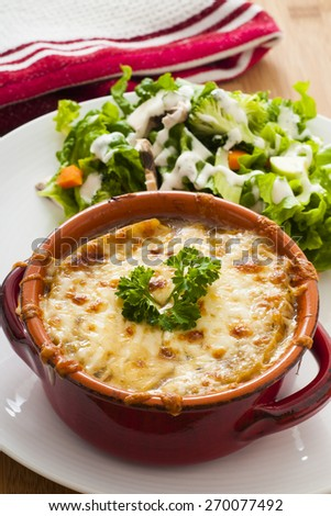 Homemade baked French Onion Soup with cheese and side salad - stock photo