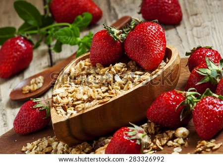 Homemade baked muesli with fresh strawberries and mint in a bowl in the shape of a heart, selective focus - stock photo