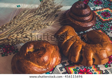 Homemade baking. Cheesecake with cherry, croissant with jam, bun Snail with poppy seeds and barley spikes on the embroidered tablecloth in ethnic style.
