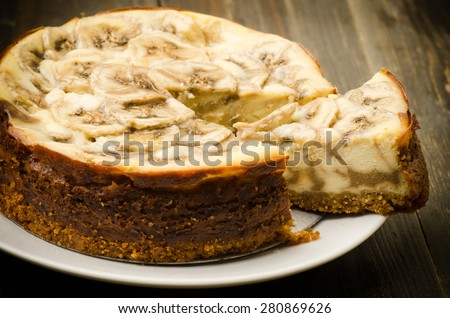 Homemade banana caramel cheesecake on plate and wooden background - stock photo