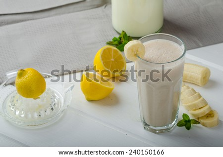 Homemade banana smoothie with lemons, herbs and organic milk from the farm