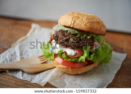 homemade beef burger with lettuce, tomato and fried bacon on wooden background