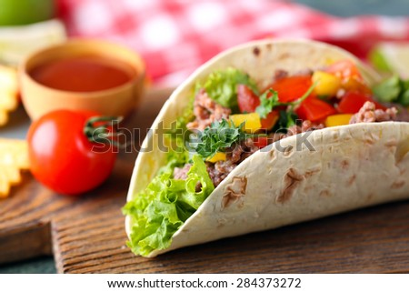 Homemade beef burrito with vegetables, potato chips on cutting board, on wooden background