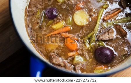 Homemade beef stew in a blue enamel stock pot on a wooden table.  - stock photo
