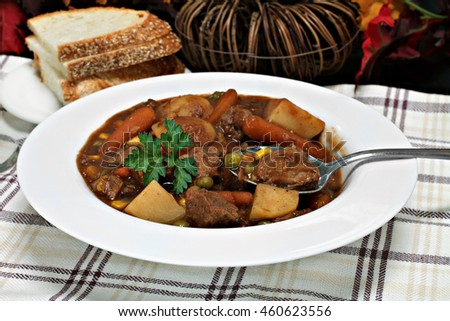 Homemade beef stew with carrots, beef, potatoes, peas and a red sauce.  Selective focus on spoon.