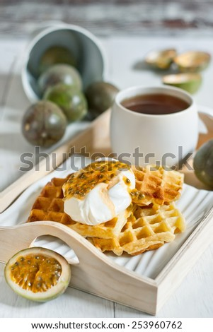 Homemade belgian waffles with cream and passionfruit pulp. Selective focus. - stock photo