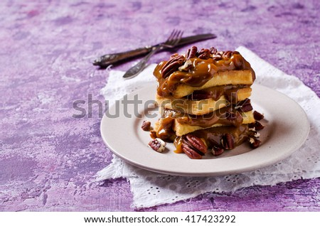 Homemade Belgian waffles with thick caramel and nuts. Selective focus. - stock photo