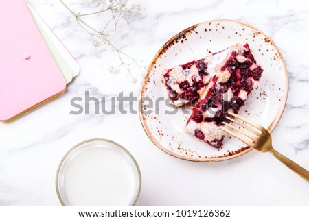 Homemade berries sponge cake slices served on white plate, cup of milk and white flowers on grey marble table. Summer breakfast. Selective focus