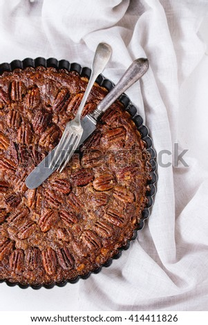 Homemade Big round caramel pecan pie in black iron forms, served with vintage cutlery on gray textile rag over white stone textured background. Flat lay. - stock photo