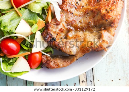 Homemade black pepper pork chop steak with salad on white plate. Over wooden table with top view.