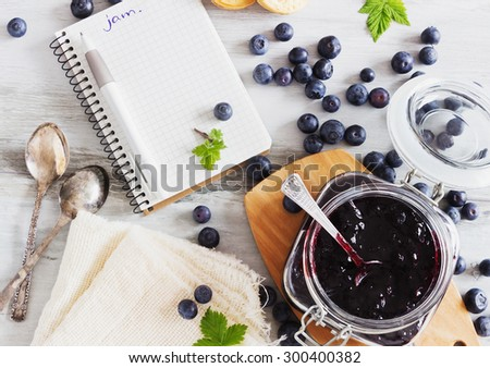 homemade blueberry jam in a jar and fresh blueberries on a table. a place for an inscription. health and diet concept - stock photo