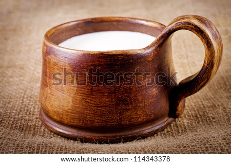 homemade brown clay cup with milk on jute background