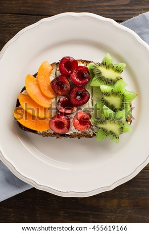 Homemade Bruschetta with fresh fruits - apricot, cherries, kiwi, salted feta cheese and honey on a rustic wooden background, top view - stock photo