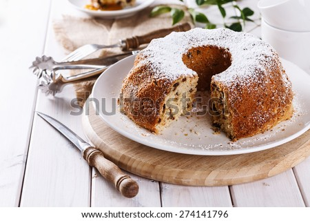 Homemade Bundt Cake with raisins dusted with icing sugar on a white plate over white wooden background. Selective focus, Shallow Depth of Field, Close up - stock photo