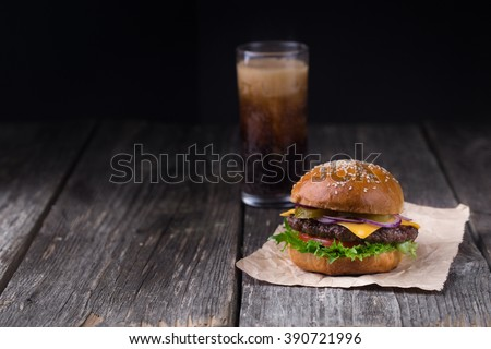 Homemade burger with beef patty, lettuce, tomato, cheese, pickled cucumbers and red onion served with glass of sparkling cola - stock photo